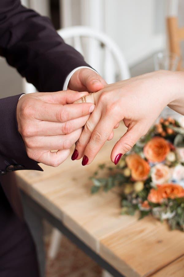Anillos de bodas y manos de la novia y del novio pares jovenes de la boda en la ceremonia matrimonio Hombre y mujer en amor dos p imagen de archivo