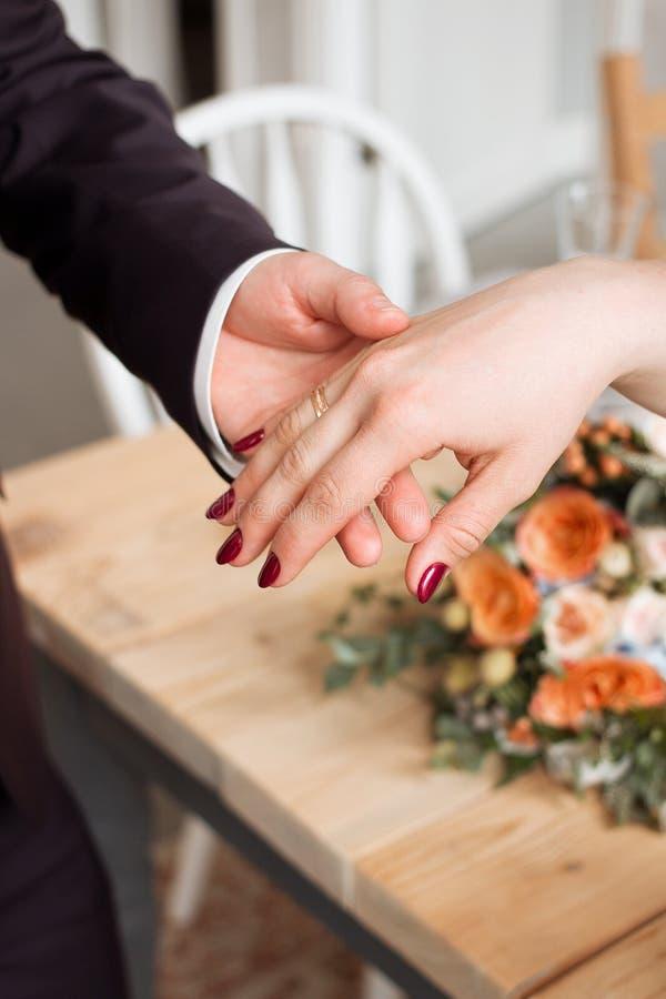 Anillos de bodas y manos de la novia y del novio pares jovenes de la boda en la ceremonia matrimonio Hombre y mujer en amor dos p fotografía de archivo