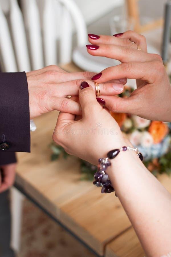Anillos de bodas y manos de la novia y del novio pares jovenes de la boda en la ceremonia matrimonio Hombre y mujer en amor dos p foto de archivo