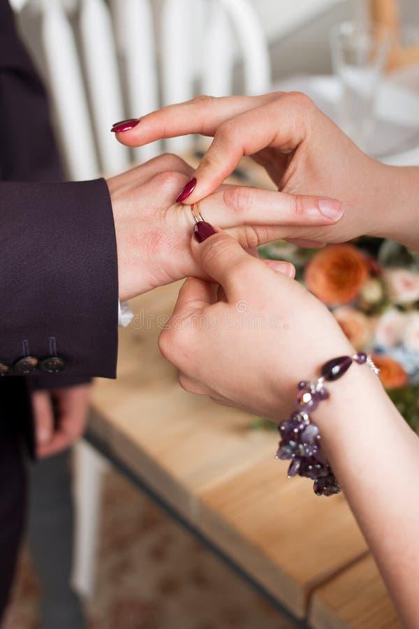 Anillos de bodas y manos de la novia y del novio pares jovenes de la boda en la ceremonia matrimonio Hombre y mujer en amor dos p foto de archivo libre de regalías