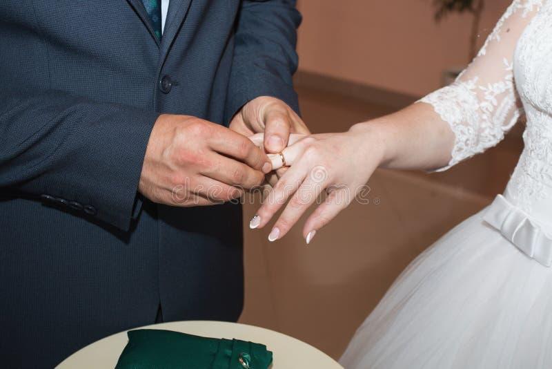 Anillos de bodas y manos de la novia y del novio pares jovenes de la boda en la ceremonia matrimonio Hombre y mujer en amor Dos fotografía de archivo