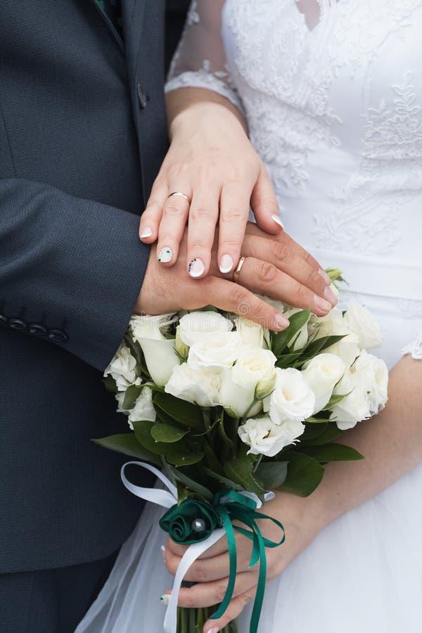 Anillos de bodas y manos de la novia y del novio pares jovenes de la boda en la ceremonia matrimonio Hombre y mujer en amor Dos fotos de archivo
