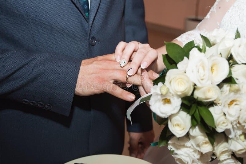Anillos de bodas y manos de la novia y del novio pares jovenes de la boda en la ceremonia matrimonio Hombre y mujer en amor Dos fotografía de archivo libre de regalías
