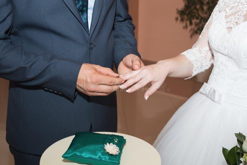 Anillos de bodas y manos de la novia y del novio pares jovenes de la boda en la ceremonia matrimonio Hombre y mujer en amor Dos imágenes de archivo libres de regalías