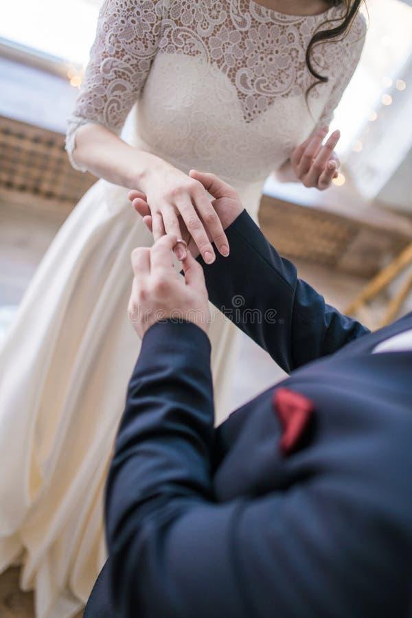 Anillos de bodas y manos de la novia y del novio imagen de archivo