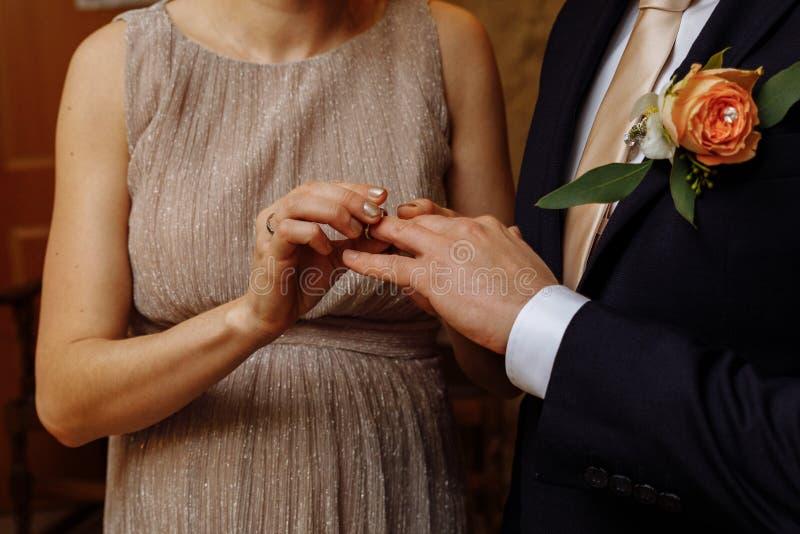 Anillos de bodas y manos de los recienes casados fotos de archivo