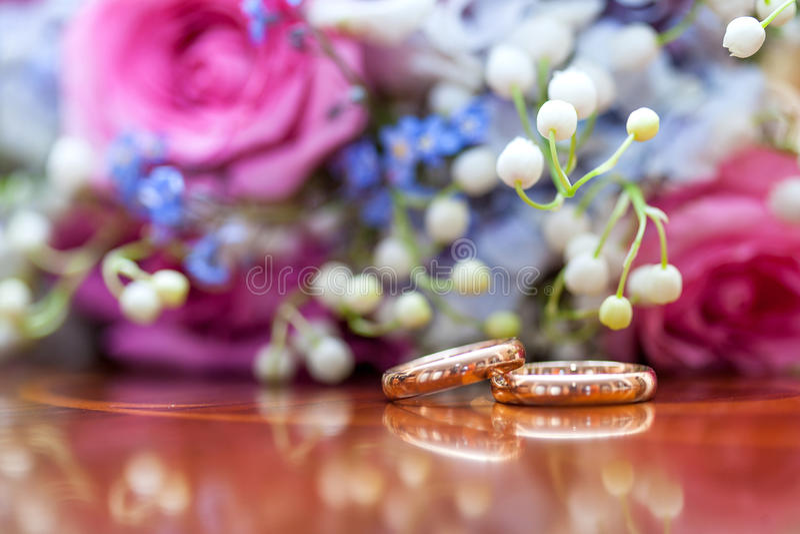 Anillos de bodas y ramo imagen de archivo