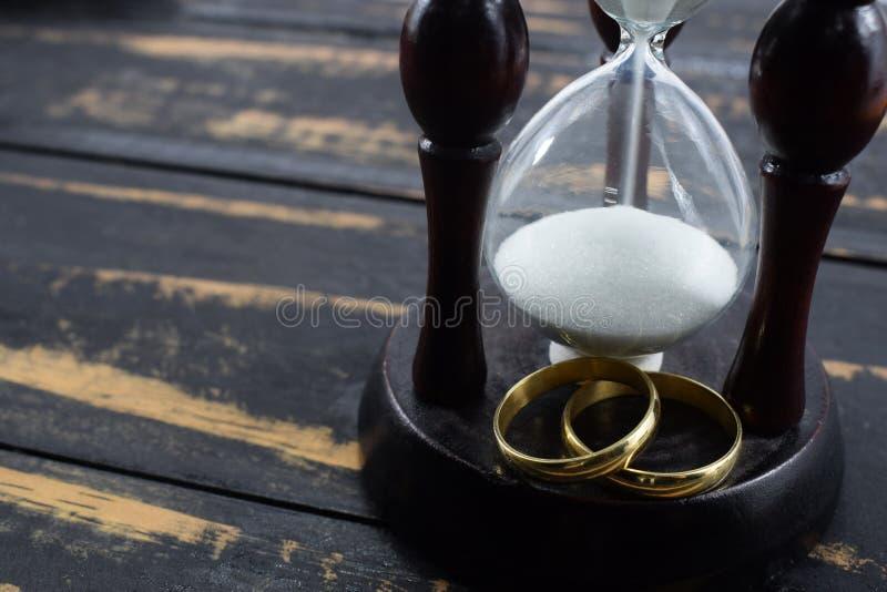 Anillos de bodas y reloj de arena junto para siempre mientras que la muerte no nos divide imagenes de archivo