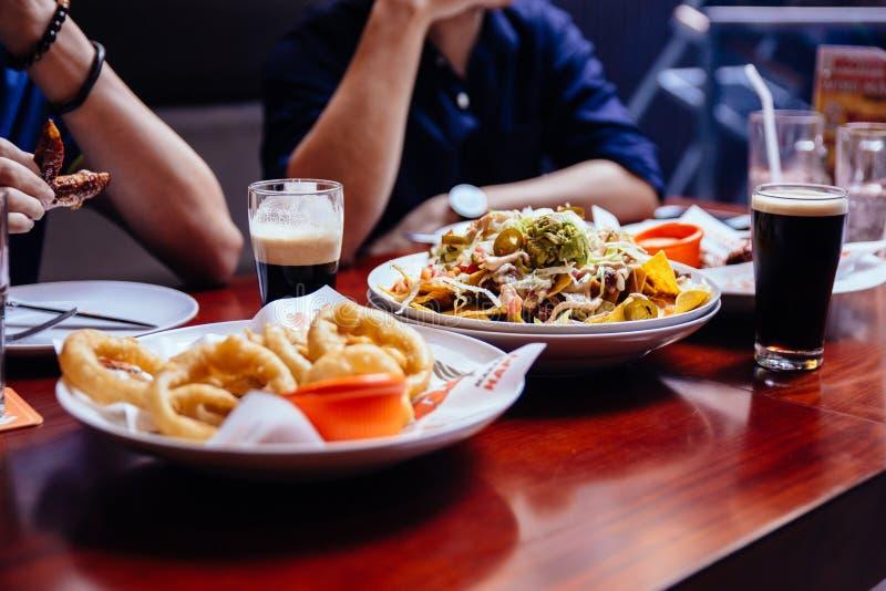 Anillos de cebolla, ensalada de Nach y pinta de cerveza negra valiente en la tabla de madera en la barra imagenes de archivo