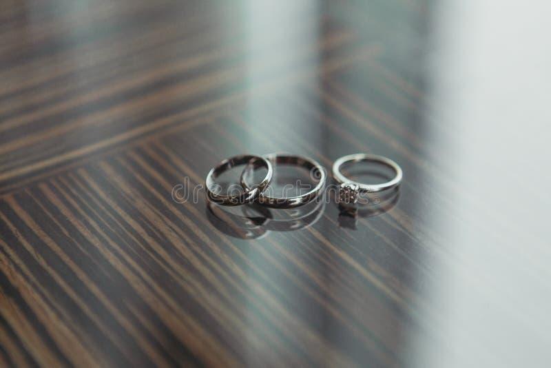 Anillos de compromiso de los anillos de oro del diamante de la boda en la tabla imagen de archivo libre de regalías