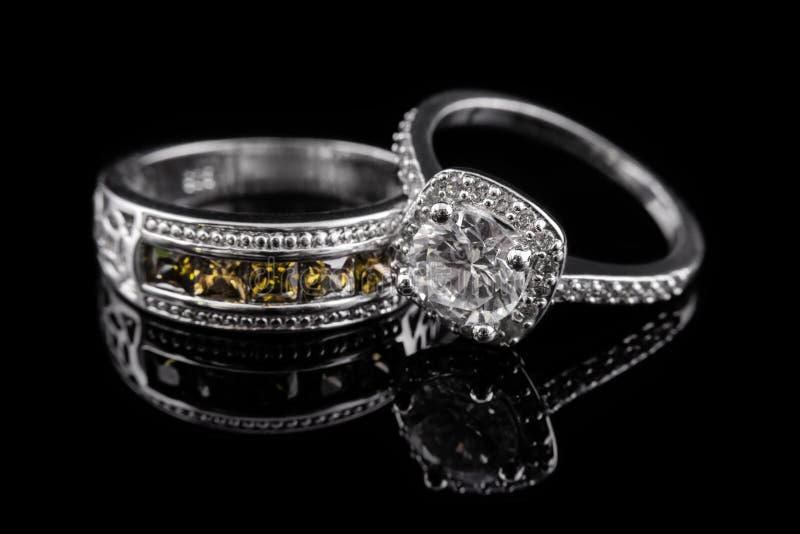 Anillos de compromiso del oro de plata o blanco con las gemas amarillas y diamantes en fondo de cristal negro imagenes de archivo