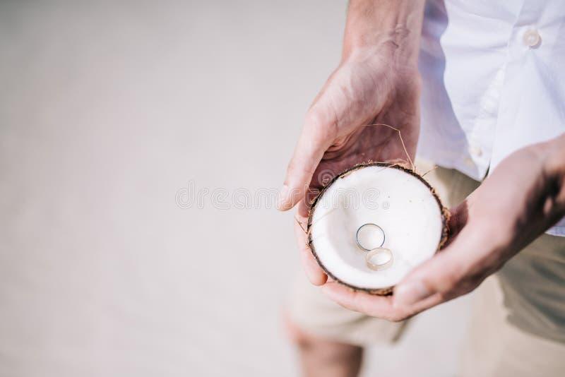 Anillos de compromiso dentro del coco en la playa tropical imagen de archivo libre de regalías