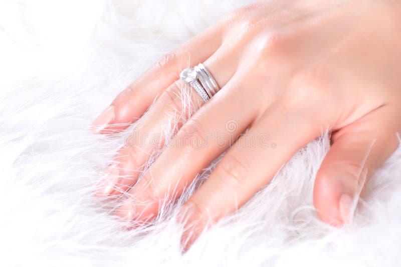 Anillos de compromiso de los diamantes en la mano femenina joven y la piel blanca imagen de archivo