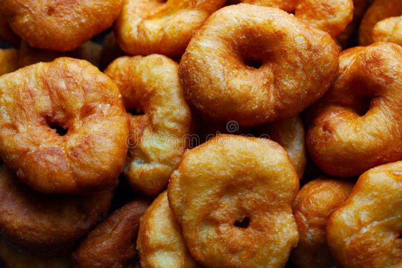Anillos de espuma dulces de oro fritos en el aceite de girasol, el cocinar rápido de la comida dañina de la calle imagenes de archivo