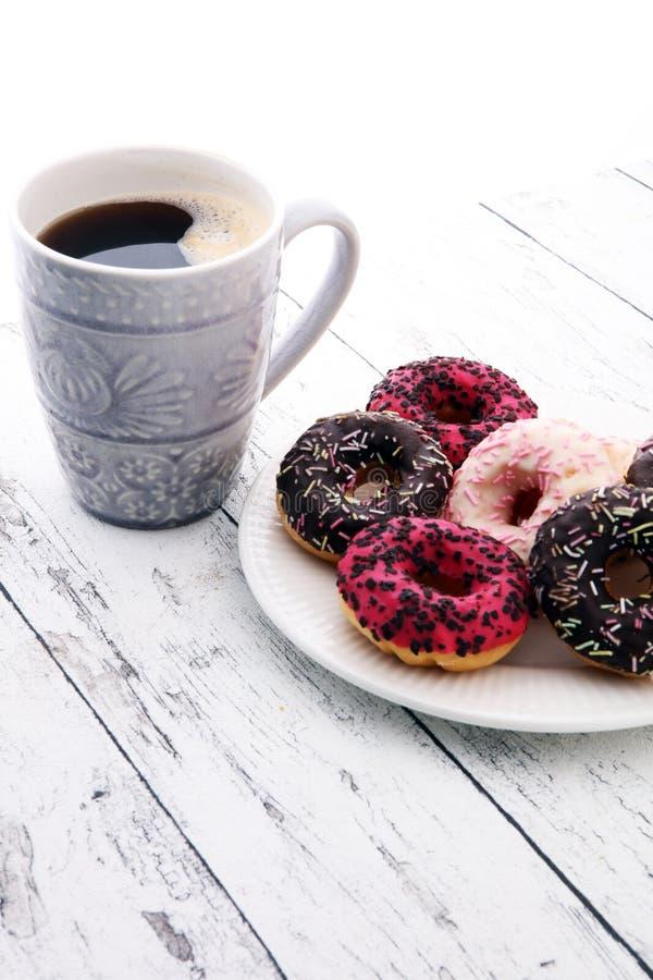 Anillos de espuma y café para un desayuno dulce en fondo de madera fotografía de archivo