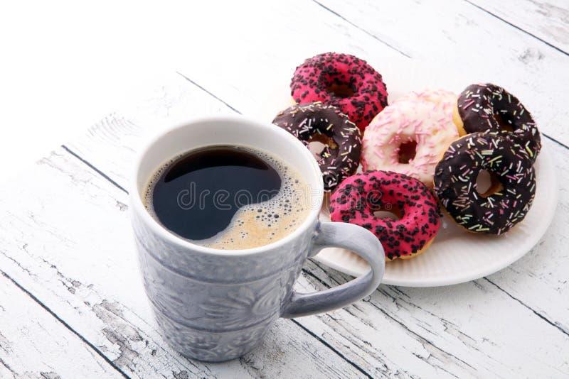 Anillos de espuma y café para un desayuno dulce en fondo de madera fotos de archivo