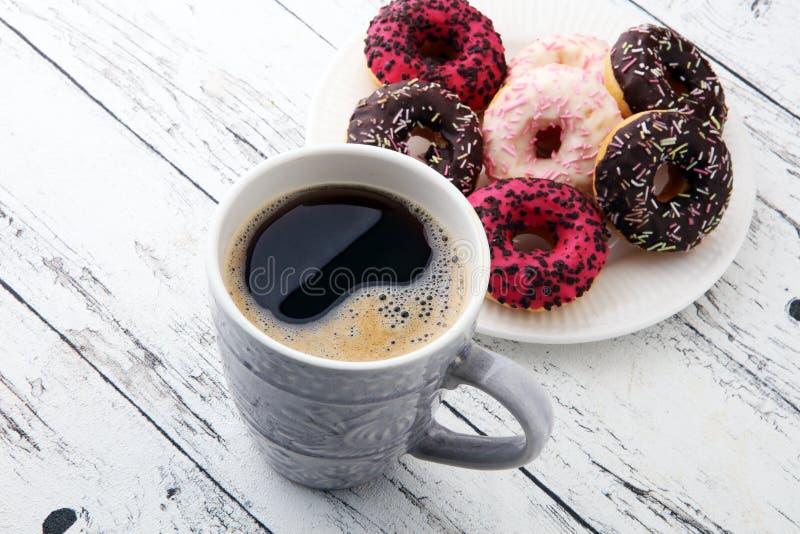 Anillos de espuma y café para un desayuno dulce en fondo de madera imagenes de archivo