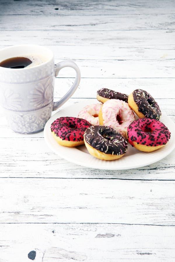 Anillos de espuma y café para un desayuno dulce en fondo de madera imagen de archivo