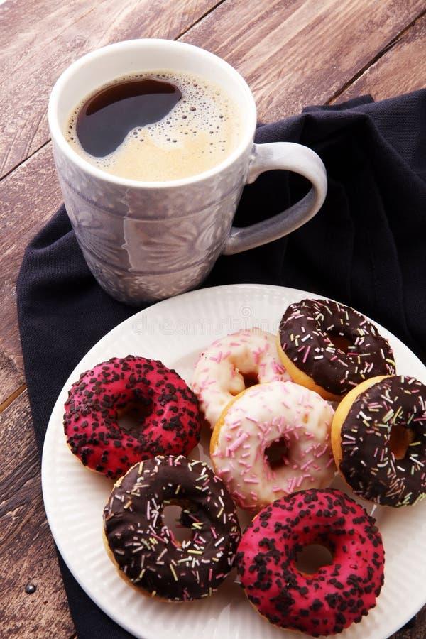 Anillos de espuma y café para un desayuno dulce en fondo de madera imágenes de archivo libres de regalías