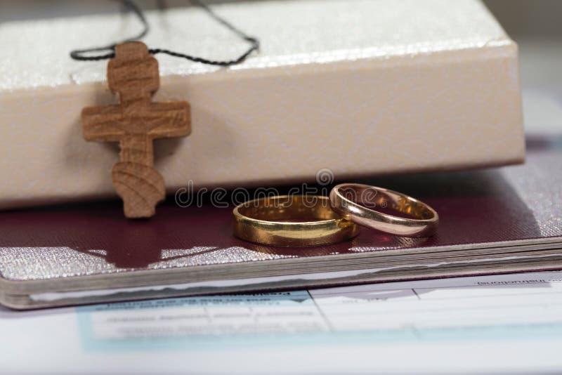Anillos de la boda cerca de la biblia con la cruz de madera imagen de archivo libre de regalías