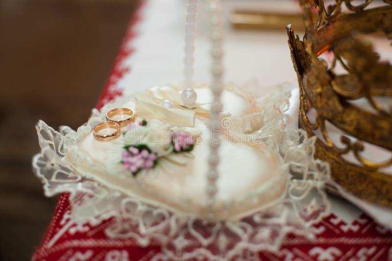 Anillos de oro clásicos de la ceremonia de boda en una almohada en el viejo chu fotos de archivo