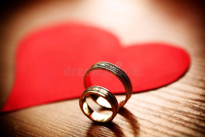 Anillos de oro de la boda hermosa con un corazón imagen de archivo