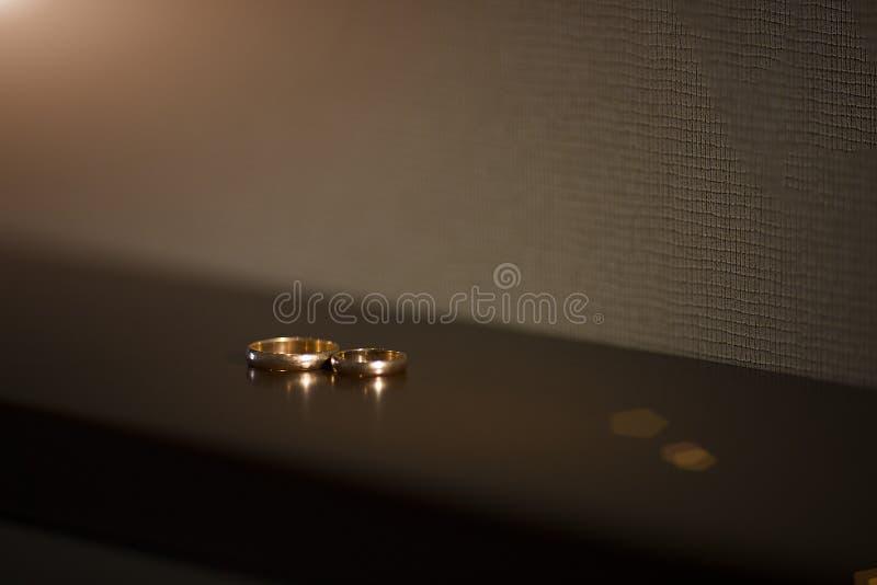 Anillos de oro en una tabla de madera fotos de archivo