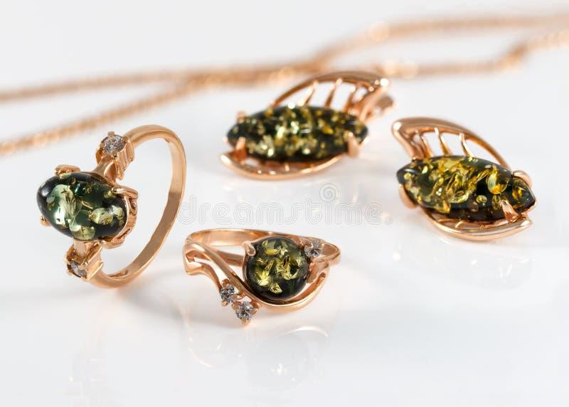 Anillos y pendientes de oro del primer con el ámbar verde báltico natural auténtico en superficie de acrílico imágenes de archivo libres de regalías
