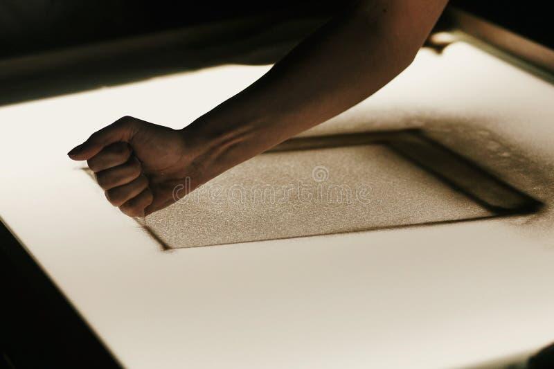 Animação da areia no copo de água Desenho da mão na areia na caixa leve na sala escura, mostra criativa da areia Pintura da pesso imagem de stock royalty free