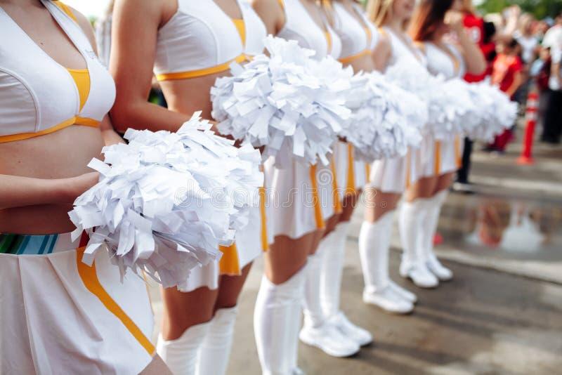 Animadoras en Pom-Poms que se sostienen uniformes del blanco Cierre para arriba Campeonato del fútbol imagen de archivo libre de regalías