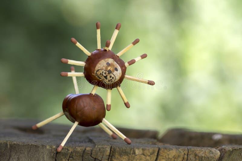 Animal divertido de la castaña dos en el tocón de árbol, fondo verde, artesanía tradicional del otoño, león imágenes de archivo libres de regalías