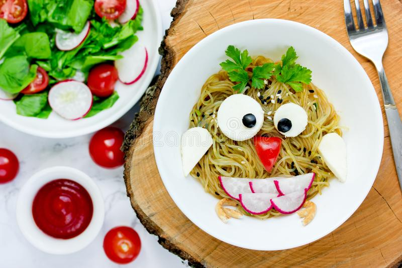 Animal shaped funny food for kids, owl pasta. With sauce, vegetables and cheese stock photo