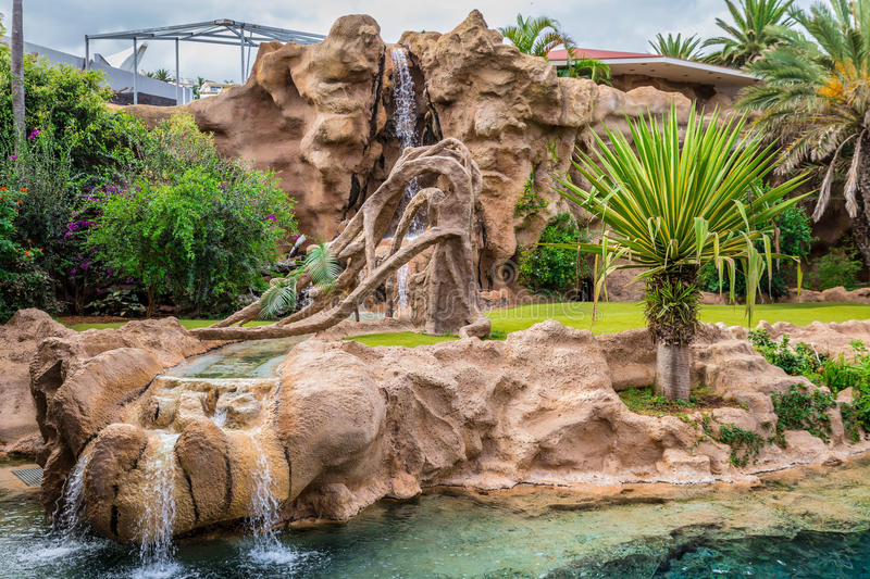 Animal Zoo Enclosure. Big animal enclosure in a zoo with a waterfall royalty free stock photo