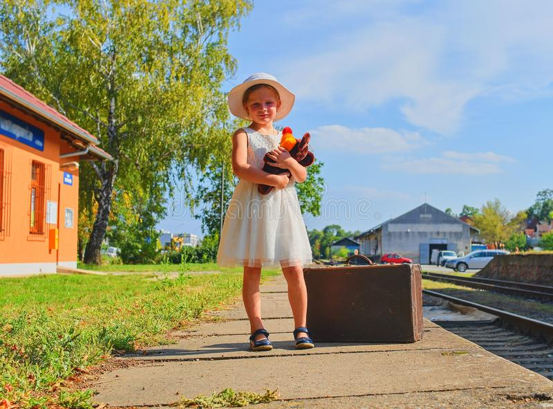 Animale farcito della tenuta sveglia della ragazza su una stazione ferroviaria, aspettante il treno con la valigia d'annata Viagg fotografie stock