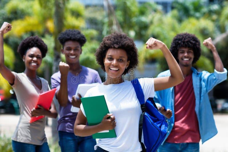 Animando uma estudante universitária africana-americana com um grupo de estudantes africanos americanos fotos de stock royalty free