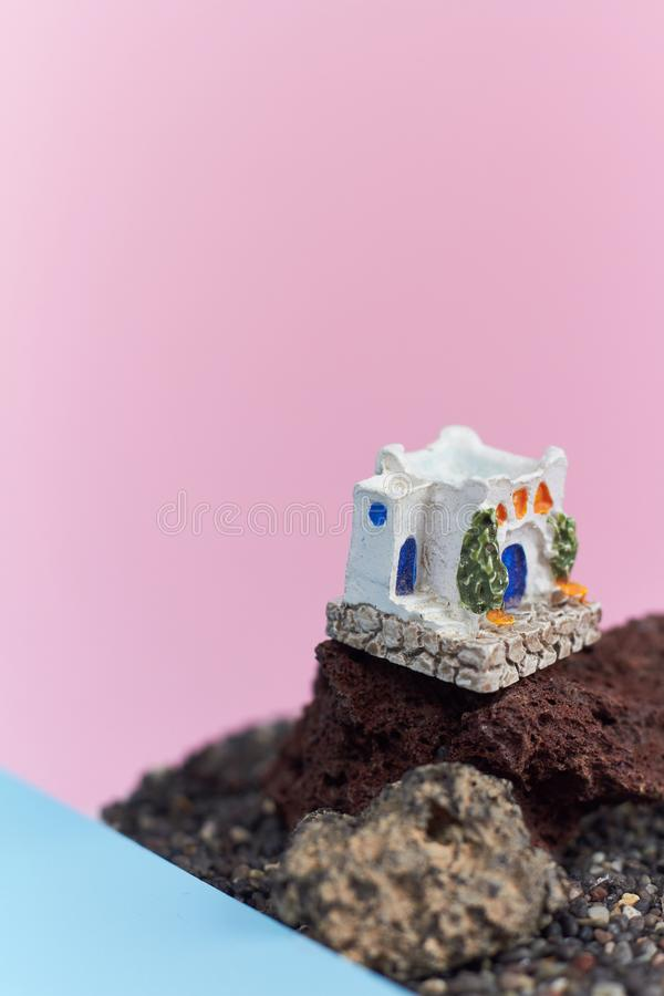 Animated model of a Greek house on a rock on a neon and pink background. stock photo