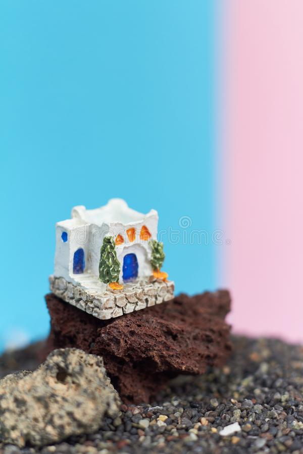 Animated model of a Greek house on a rock on a neon and pink background. stock images
