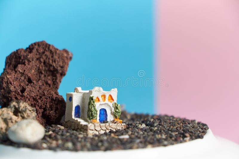 Animated model of a Greek house on a rock on a neon and pink background. royalty free stock photography