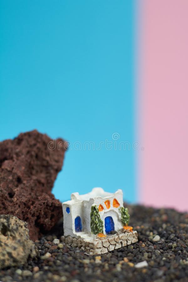 Animated model of a Greek house on a rock on a neon and pink background. stock image