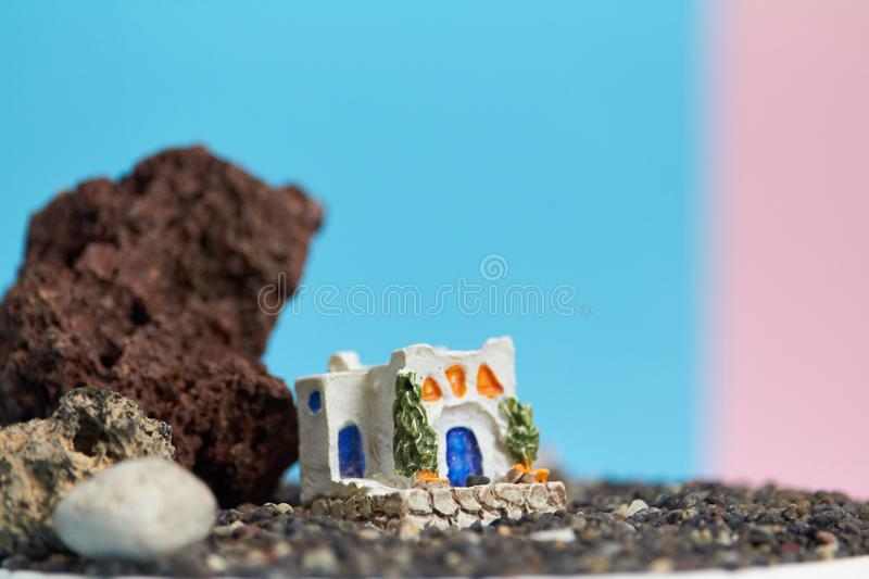 Animated model of a Greek house on a rock on a neon and pink background. stock photography