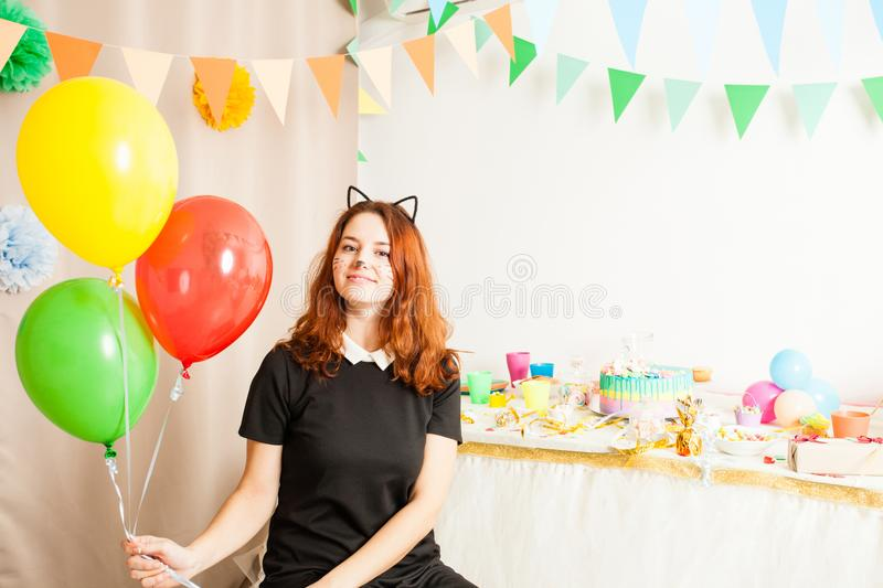 Animator for children`s holiday. Funny playful girl animator in costume of cat holding colorful balls on the birthday party royalty free stock photo