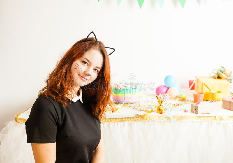 Animator for children`s holiday. Funny playful girl animator in costume of cat holding colorful balls on the birthday party royalty free stock photos