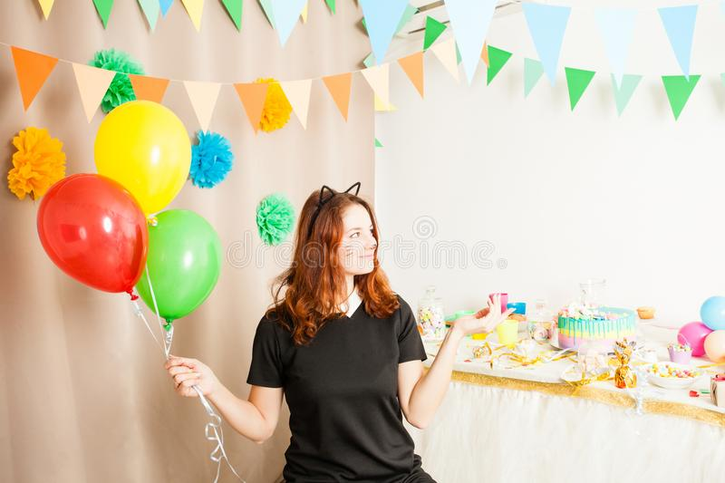 Animator for children`s holiday. Funny playful girl animator in costume of cat holding colorful balls on the birthday party royalty free stock photography
