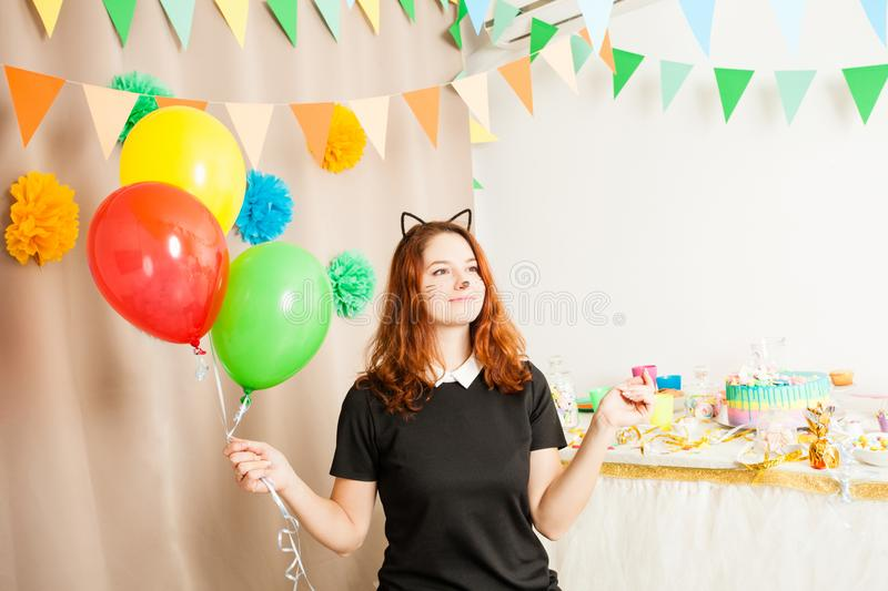 Animator for children`s holiday. Funny playful girl animator in costume of cat holding colorful balls on the birthday party stock images