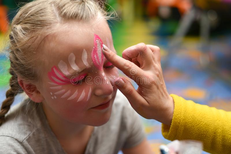Animator draws a girl drawing on the face at a party.  royalty free stock photos