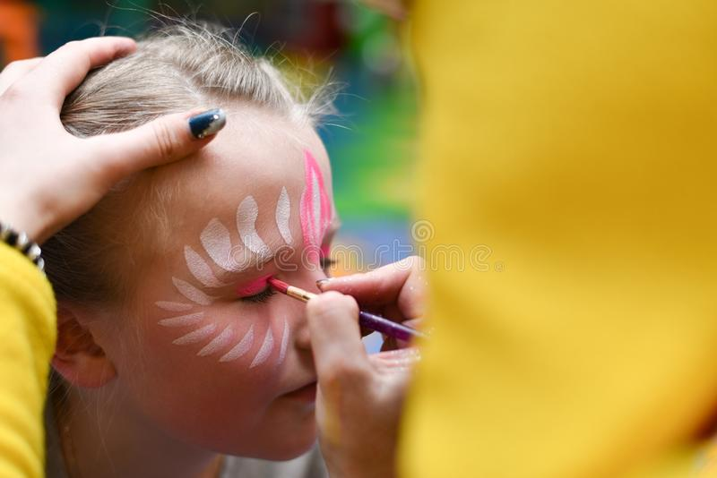 Animator draws a girl drawing on the face at a party.  stock image