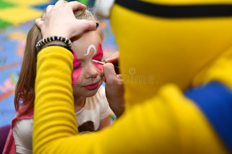 The animator paints a drawing on the face of a little girl at a party.  royalty free stock photography