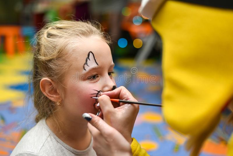 The animator paints the face of the child.  royalty free stock photography