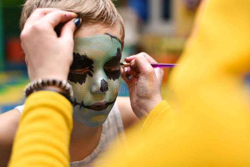The animator paints the face of the child.  royalty free stock photo