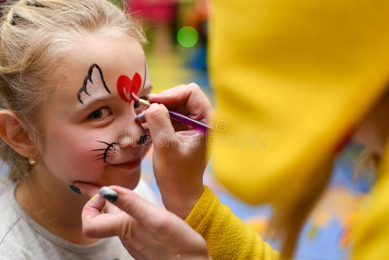 The animator paints the face of the child.  stock photo